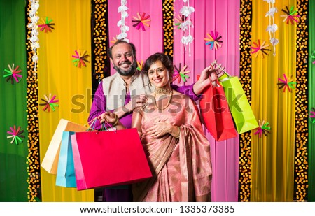 b0f5e096b4 Mid age indian couple showing in festival shopping bags in traditional  cloths with decorated background #
