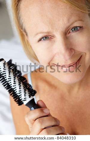 Mid age woman holding hairbrush