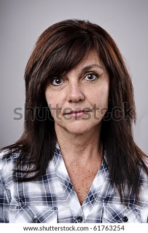 Mid age woman poses for a portrait in studio
