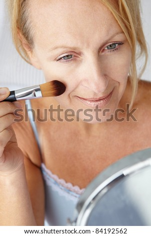 Mid age woman putting on make-up