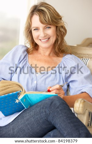 Mid age woman writing in notebook