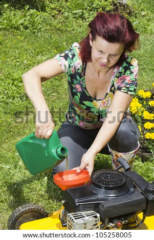 Mid age women adding oil to lawn mower