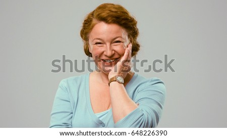 Mid aged actress showing emotions of affection. Woman in studio shows the emotion of affection. Actress with red hair shows the emotion of affection.