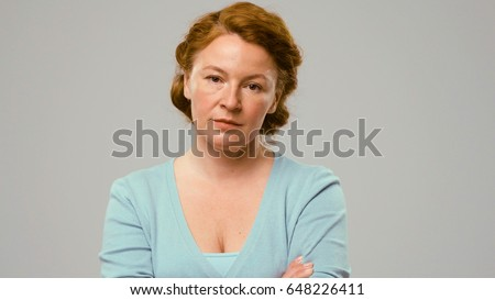 Mid aged actress showing emotions of scepticism. Actress in studio isolated on white. Actress with red curly hair shows the emotion of doubt. Woman with sceptical emotion.