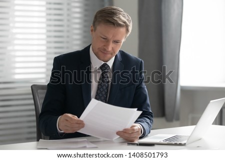Mid aged business man in suit holding read document paper report sit at office desk, company ceo doing paperwork feel satisfied with good work result receive loan approval salary payment tax refund