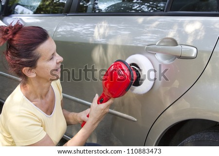 Mid aged cute woman polishing her car with electric polishing tool