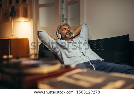 mid aged man listening music with headphones on phonograph, relaxed in sofa at his home