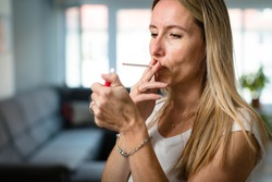 Mid-aged woman lighting a cigarette at home, getting her nicotine daily dose, unable to resist to her unhealthy habit