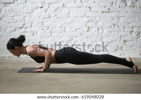Mid aged yogi attractive woman practicing yoga concept, standing in chaturanga dandasana exercise, four limbed staff, Push ups or press ups pose, working out, full length, white loft background
