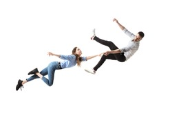 Mid-air beauty cought in moment. Full length shot of attractive young woman and man hovering in air and keeping eyes closed. Levitating in free falling, lack of gravity. Freedom, emotions, artwork