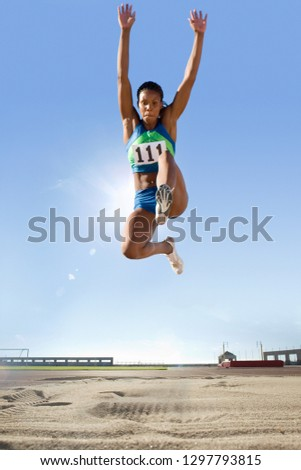 Mid-air shot of female long jumper competing in stadium event