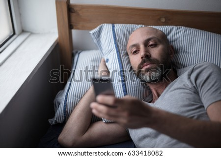 Mid forties depressed man in bed at home Stock photo ©