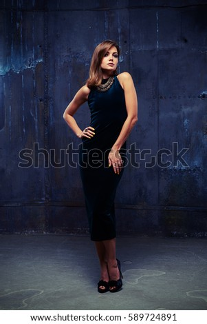Mid full-length shot of sophisticated attractive model in blue velvet dress and jewelry looking at camera. Placing hands on hips while standing #589724891