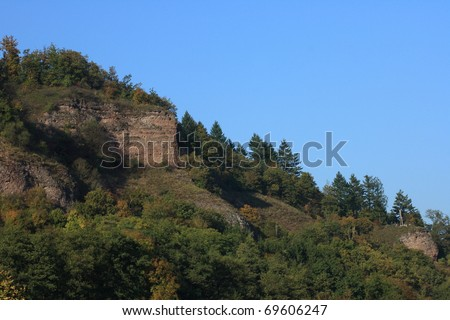 Mid-mountain landscape with trees and blue sky