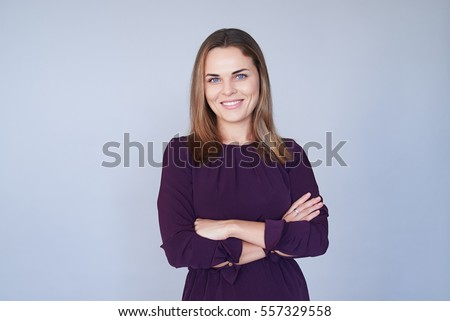 Mid portrait of charming woman over white background. Lady with folded arms looking at the camera