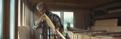 Mid 50s Caucasian male examining a hand made canoe paddle in his workshop. Boat making hobby, small business owner