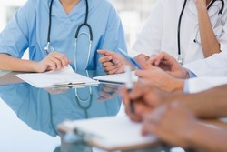 Mid section group of young doctors in a meeting at hospital