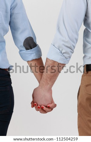 Mid section image of a couple holding hands against a white background.