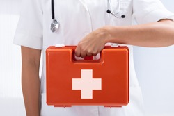 Mid-section Of A Doctor's Hand Holding Red First Aid Bag On White Background