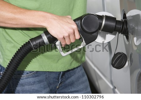 Mid section of a man refueling a car