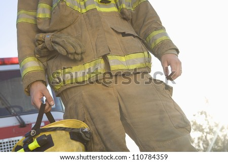 Mid section of a middle aged firefighter standing with fire brigade in the background
