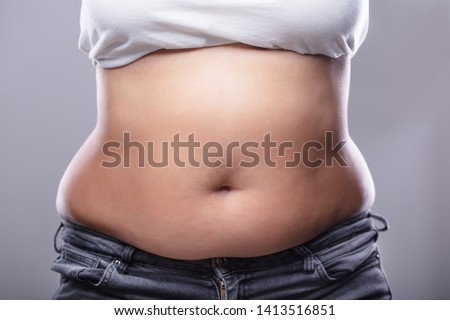 Mid Section Of A Woman With Excessive Belly Fat Against Grey Background Foto stock ©
