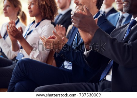 Mid section of applauding audience at business seminar
