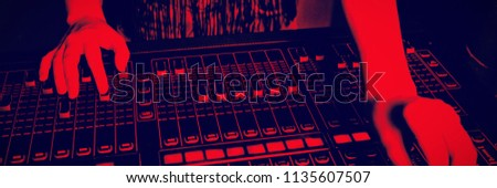 Mid section of audio engineer operating sound mixer at recording studio