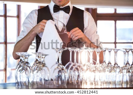 Mid section of bartender cleaning wine glass at bar counter