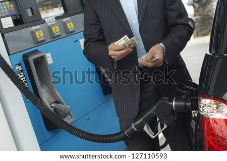 Mid section of businessman counting money with gasoline refueling car at fuel station