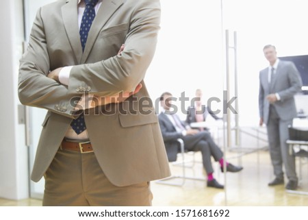 Mid section of businessman with colleagues in meeting room