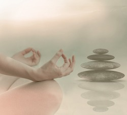 Mid section of calm young woman meditating. Zen stones in the background. Relaxing wellness holistic spa for relaxation and good health rejuvenation