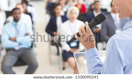 Mid section of Caucasian female speaker speaks with microphone to diverse business people in a business seminar in a conference room