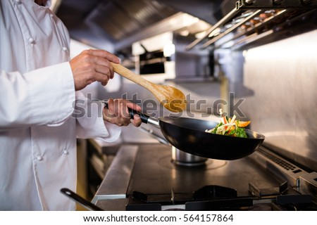 Mid section of chef preparing food in the kitchen of a restaurant