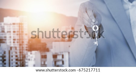 Mid section of executive showing new house key against buildings against mountain #675217711