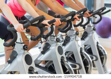 Mid section of four people working out at a class in gym