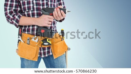 Mid section of handy man with tool belt holding a drill against blue background Stock photo ©