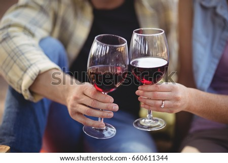 Mid section of man and woman toasting wineglasses at farm