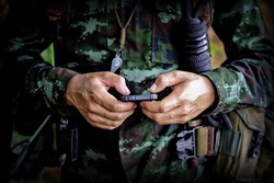 Mid section of military soldier using mobile phone in boot camp war. Historical re-enactment with a soldier and an anachronistic cell smartphone to text