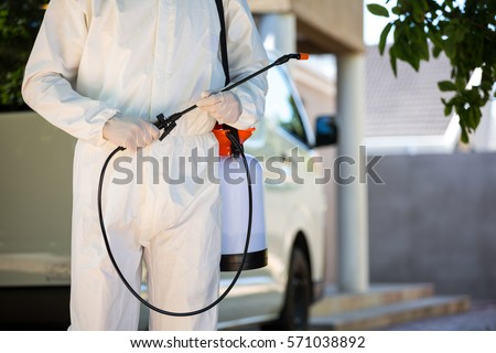 Mid section of pest control man standing next to a van on a street #571038892