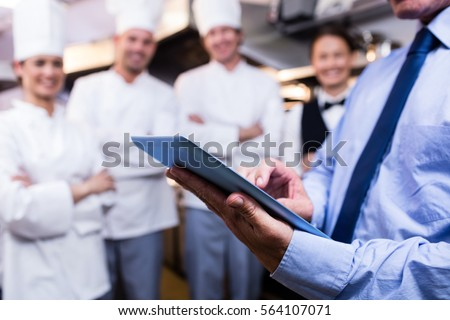 Mid section of restaurant manager using digital tablet in commercial kitchen #564107071