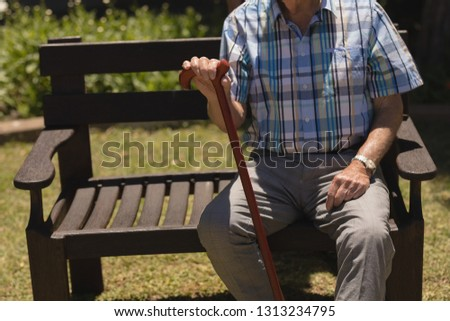 Mid section of senior man sitting with cane on bench in garden in sunshine