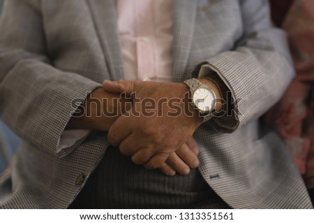 Mid section of senior man with folded hands at nursing home