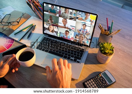 Mid section of teacher having a video conference with multiple students on laptop at school. distance learning online education concept