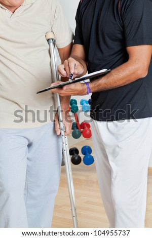 Mid section of trainer holding clipboard while standing with senior man on crutches