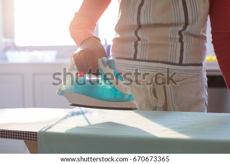 Mid section of woman ironing shirt on ironing board in kitchen at home #670673365