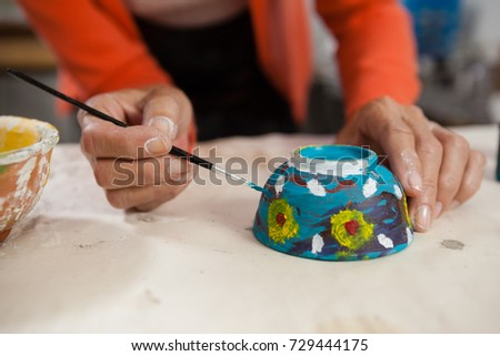 Mid section of woman painting bowl in class