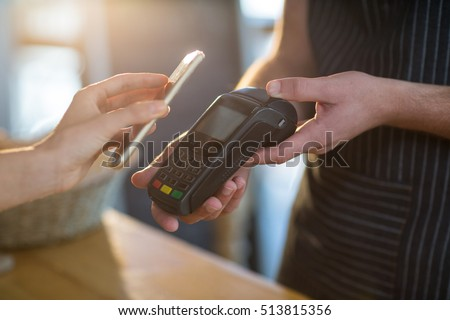 Mid-section of woman paying bill through smartphone using NFC technology in cafe