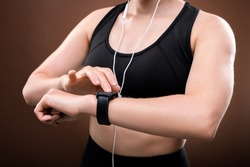Mid section of young sportswoman in activewear and earphones switching on her fitbit on wrist before outdoor jogging workout