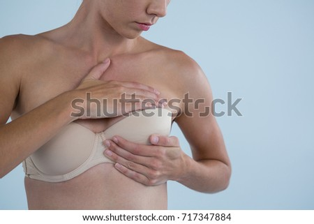 Mid section of young woman checking for breast cancer lumps while standing against gray background